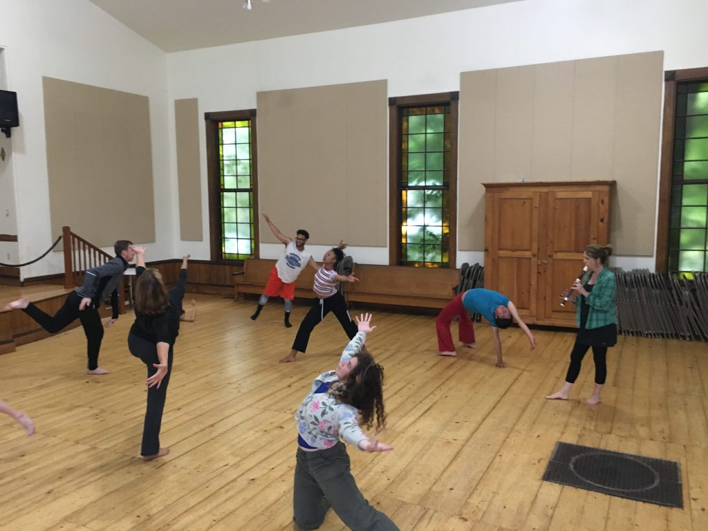 Scattered individuals dancing in an open hall with wood floors