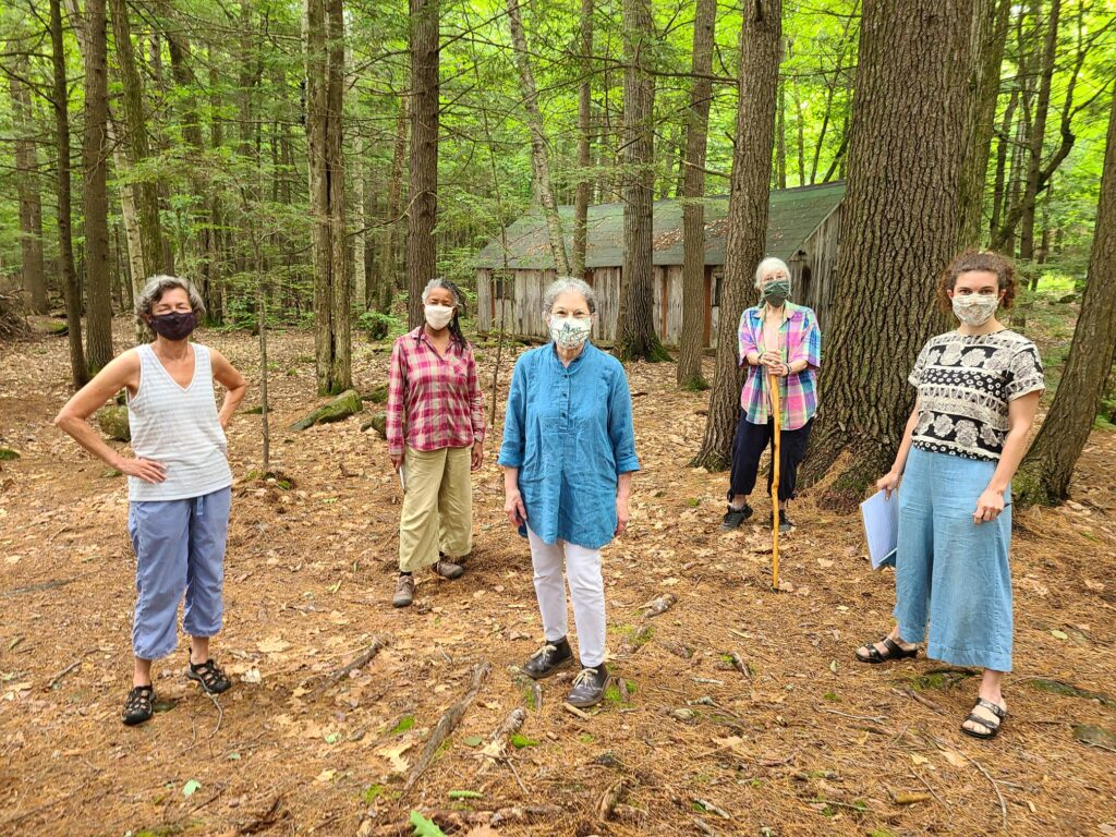 A gathering of board, staff, and advisory council members stand tall spaces out among the trees. they wear face masks and brught colors that stand out with the brown background of bark, pine needles and a wooden long building behid and around them.